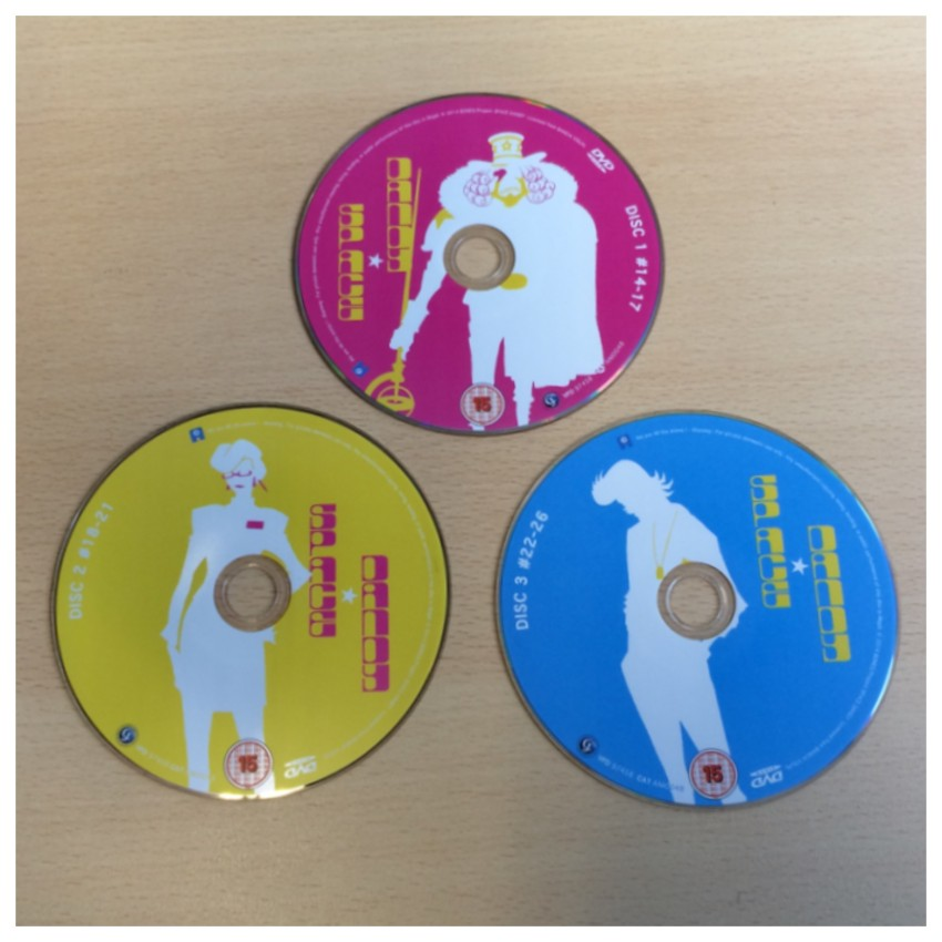 The three DVD discs inside the Amaray case. (NOTE: Blu-ray version is two discs total, using the pink disc and yellow disc art.)