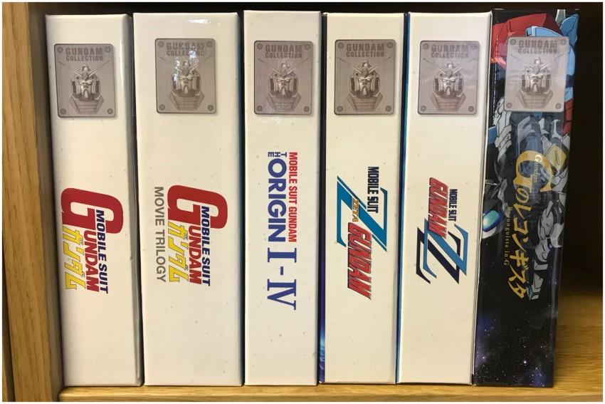 The rigid case next to previous Gundam releases* of ours that have been released. (*Sold separately)